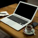 Foto de una mesa de escritorio con ordenador, café y bloc de notas.