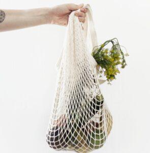 Mano sujentado una bolsa de algodón con verduras